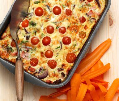 En matig och utsökt omelett som tillagas i ugn med kassler, persilja och körsbärstomater. Rör ihop ingredienserna och låt sedan kassleromeletten sköta sig själv i ugnen. Passar perfekt som brunch.