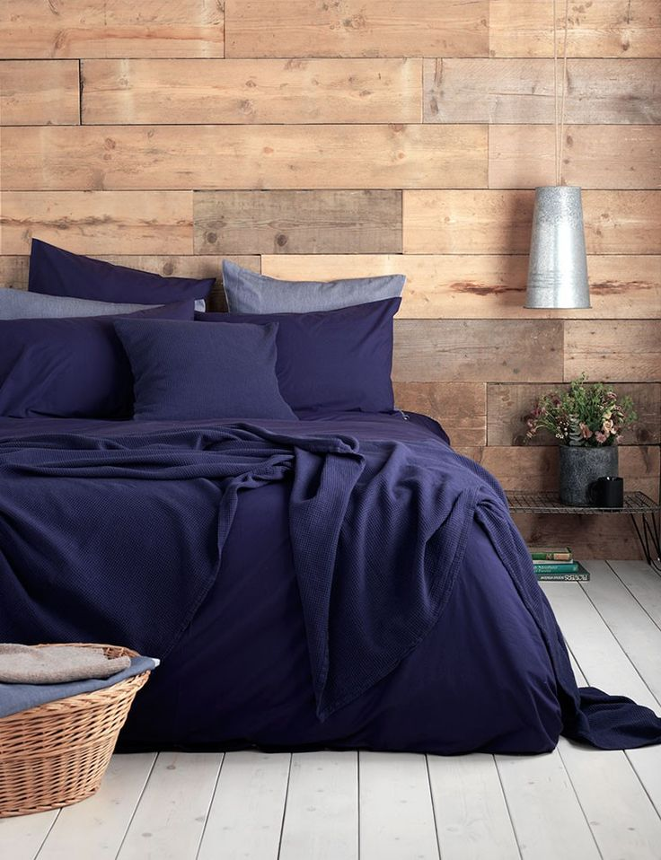 Navy blue bedding in a rustic bedroom. Our ever so soft 100% cotton, laundered soft finish.