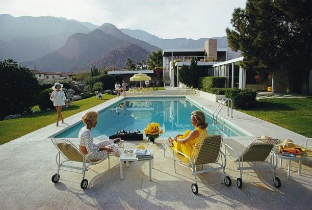 'Poolside Gossip'  The quintessential classic Slim Aarons photograph.  Available as a Ctype print in various sizes and framing options from GALERIE PRINTS.  A desert house in Palm Springs designed by Richard Neutra for Edgar J. Kaufmann. Lita Baron approaches on the right Nelda Linsk, wife of art dealer Joseph Linsk who is talking to a friend, Helen Dzo Dzo. Original Artwork: A Wonderful Time – Slim Aarons (Photo by Slim Aarons)