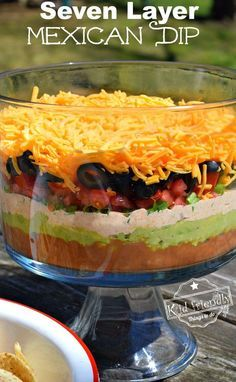 Easy and Delicious Seven Layer Mexican dip. Perfect appetizer for large crowds, parties and barbeques! www.kidfriendlythingstodo.com