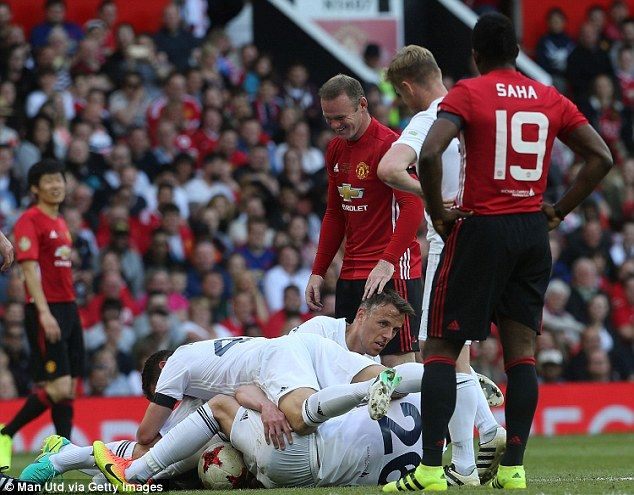 Rooney laughs as Carrick is jokingly bundled over by John Terry and Phil Neville