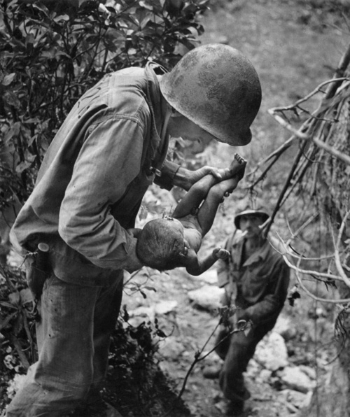US Marine holding a wounded and dying baby found in the mountains ~ Battle of Saipan Island ~ June 1944 ~ Photo by w. Eugene Smith