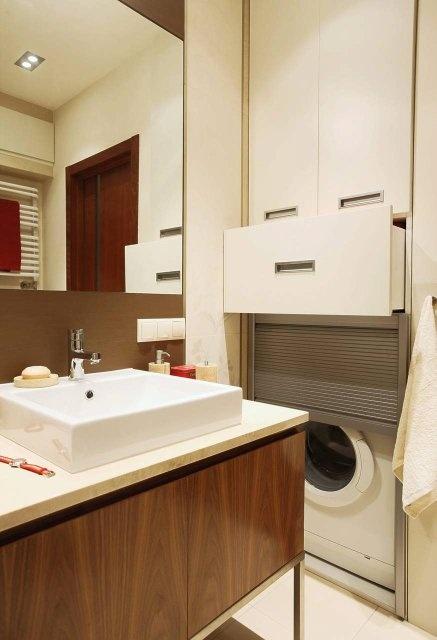 SCHOWKI. Kosztem przedpokoju dobudowano do łazienki wnękę, którą w całości zabudowano. Mieści się w niej pralka, a nad nią duża szafka w wygodną głęboką szufladą.