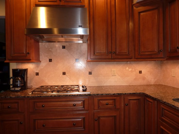 brown granite with dark mahogany cabinets and travertine backsplash