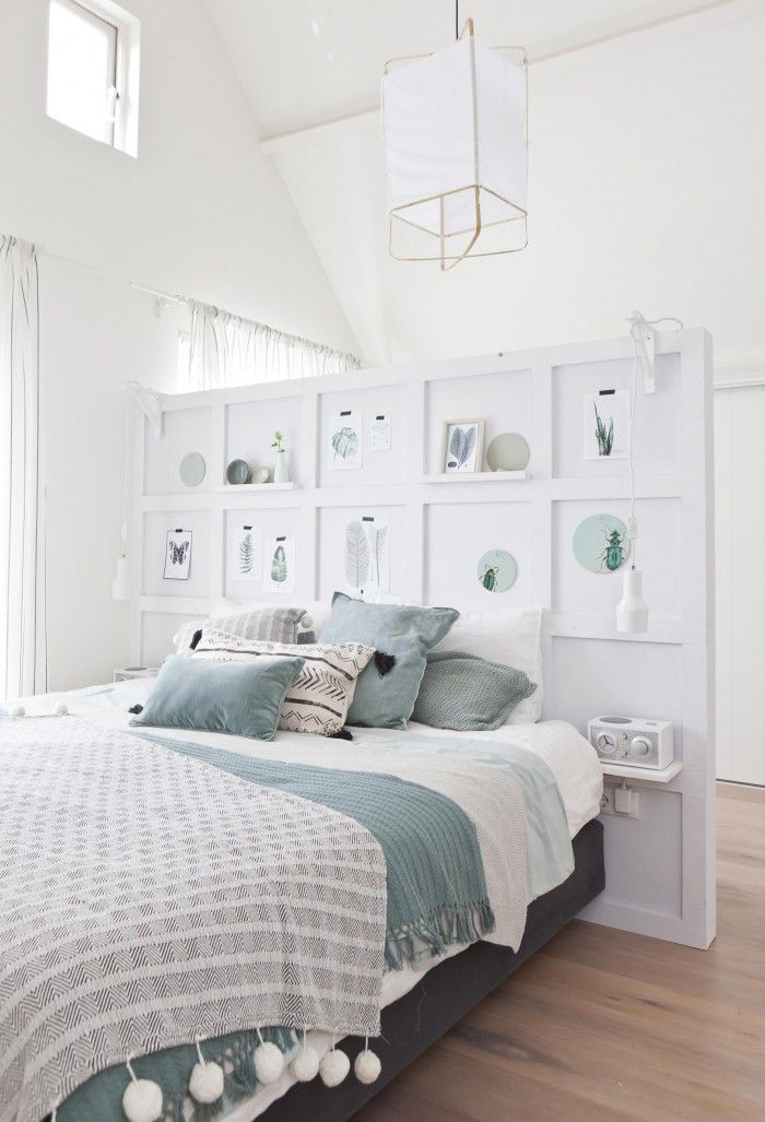 Vakkenwand als hoofdeinde en als scheiding tussen het slaap-  en het werkgedeelte van de kamer; botanische printen, groen [vtwonen].