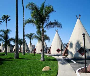 "Wigwam Village. In the heyday of the national auto craze, when Route 66 was the ""Mother Road,"" a man named Frank Redford had the idea that motorists would make a roadside stop when an attraction was visually startling. Redford's concrete teepees (each containing an individual motel room) encircled a larger teepee housing a restaurant, gift shop, and gas station."