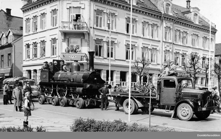 """Lokomotiv nr. 16  fraktes på lastebil gjennom Torggata i Hamar fra Jernbanemuseet til Hamar jernbanestasjon,  i forbindelse med Byjubileet 1949. Lastebil D-604 trekker toget på en spesialbygd tilhenger. Lastebilen er en Klöckner-Deutz S 3000. Lastebilen tilhører """"Billigbudene"""" @ DigitaltMuseum.no"""
