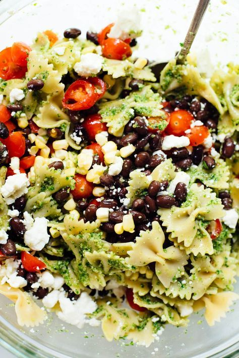 Healthy summertime pasta salad, made with jalapeño-cilantro pesto, cherry tomatoes, corn, black beans and feta. You'll love this surprising combination! #vegetarian