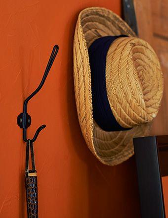 Detalle de un gorro de paja colgado en la pared junto a un gancho de IKEA.