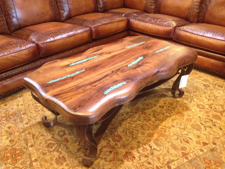 Add a work of art to your living area with a mesquite wood coffee table. It is detailed with inlaid turquoise resin and has an ornate iron base.