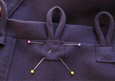 DJ5: Similar to the button loops, these are toggle button closures. They are typically found in jackets, as my wool jacket has the same detail as well. It looks like after the loop is sewn to the jacket, a small piece of self fabric is sewn on top of the ends of the loop.