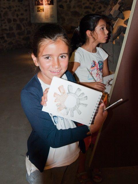 Neskato batek gurpil hidraulikoari museoan egindako marrazkia erakusten digu. / Una jovencita nos muestra el dibujo  de la rueda hidráulica hecho en el museo.