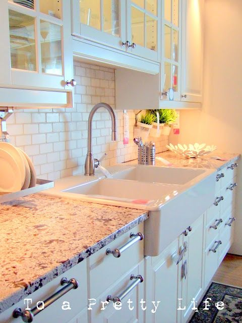 White with colored accents in counter top, large sink with two tubs, white cabinets