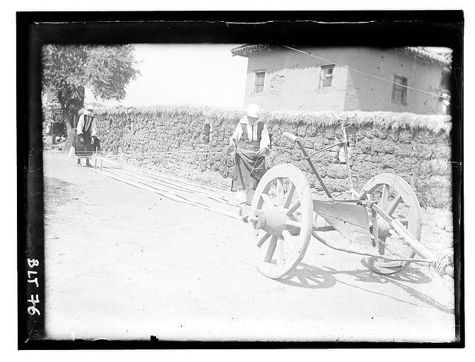 Grèce ; Macédoine ; Negocani (Νίκη-Φλώρινα)  (1916-1917) Légende Jeunes femmes s'occupant à préparer les fils de chaîne pour le tissage. En second plan, mur en terre battue et paille Auteur photoBlanchet, Joseph