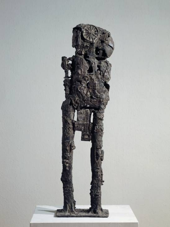 """Sir Eduardo Paolozzi, """"Cyclops"""", 1957, bronze. """"The skin of this lumbering bronze figure is imprinted with broken machine-parts and other industrial debris. Paolozzi made it by pressing pieces of metal into a bed of moist clay, and then pouring molten wax into the clay mould. He constructed the model from these sheets of wax forms and finally cast it in bronze."""""""