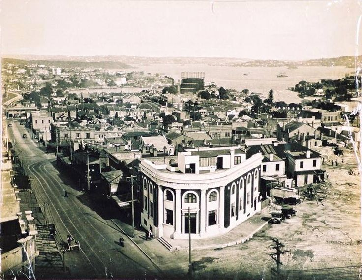 Clear image of Bank of NSW at corner of Mount Street and Pacific Highway. Neutral Bay gasometers directly in line beyond. Careening Cove on right and house complexes in between. c1931 (North Sydney Council)