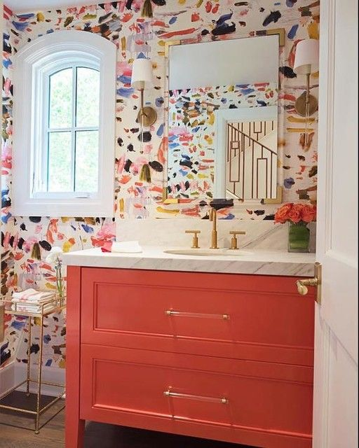 Painted pink/coral bathroom cabinet. Lucite mirrors and handles with gold trim. White marble countertop and gold faucet fixtures. Love the modern, abstract wallpaper.