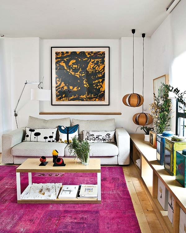 perfect little living room with bright pink over-dyed rug, neutral sofa, big artwork