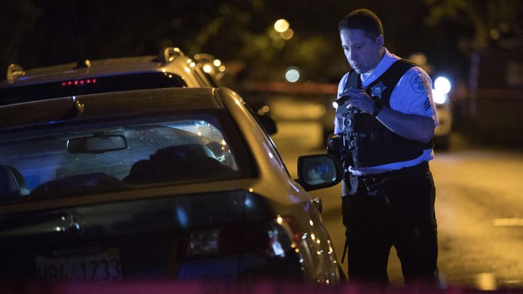 Violence leaves about 60 shot, 8 of them dead, for July 4th weekend  -  July 4, 2017:     Saturday - West LeMoyne Street  -        A Chicago police officer looks at a car at the scene of a shooting in the 2000 block of West LeMoyne Street on July 1, 2017, in Wicker Park.