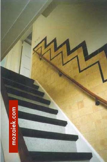tegellambrisering jaren 30 langs de trap. met zwarte tegels met afgeronde bovenzijde