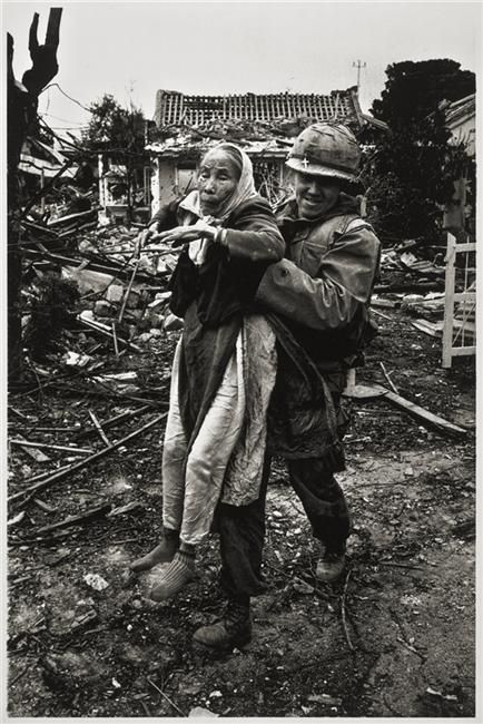 A US Army chaplain evacuates an elderly Vietnamese woman during the Tet Offensive, Hué, South Vietnam, 1968, photograph by Don McCullin.