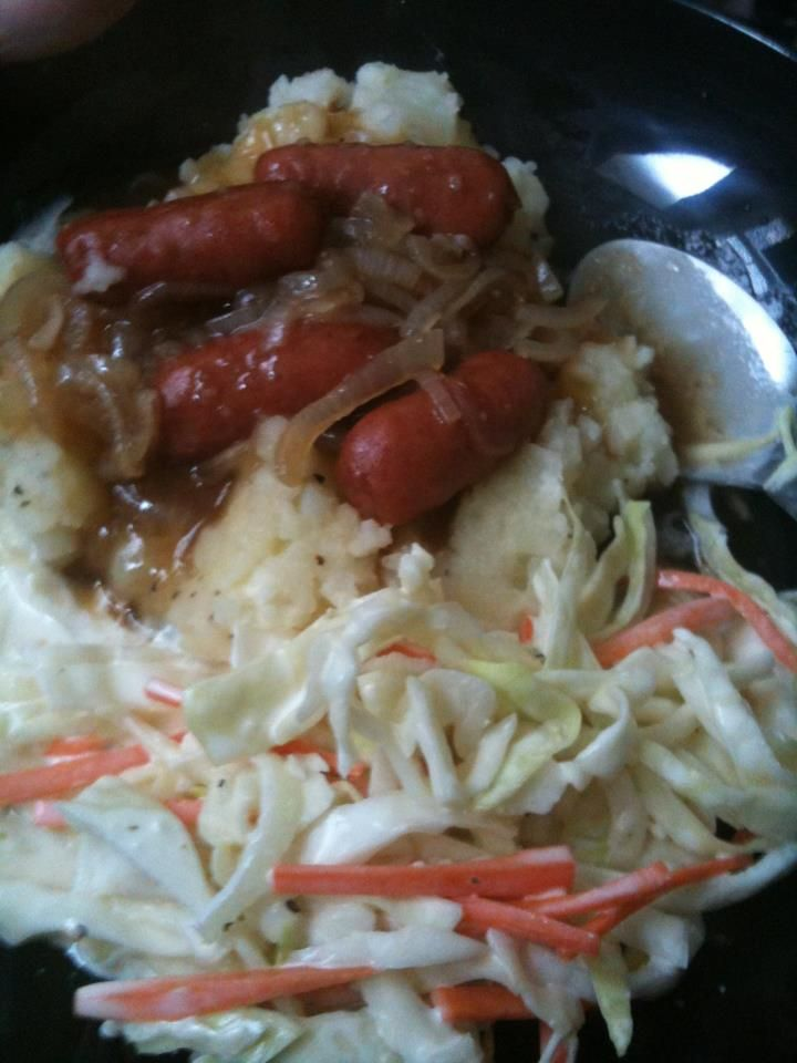 Bangers and Mash; American adaptation. Bangers (sausages with onion gravy over potatoes). This is usually served with peas, but I made cole slaw. I also didn't have real bangers, but my local grocery store now carries real Irish bangers!