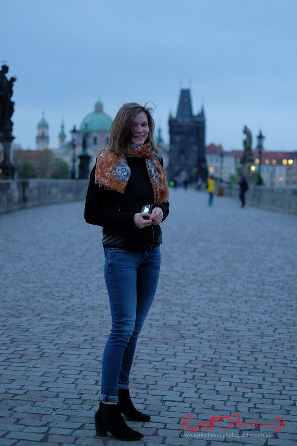 A young red haired woman on the Charles Bridge, Prague at 5:51AM wearing black suede ankle boots and jacket with blue jeans and apricot floral scarf. Street Fashion Sydney - Prague, photographed by Kent Johnson.