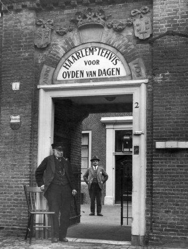 Haarlems Tehuis voor Ouden van dagen, huidig Dolhuys, voormalig leprozenhuis, aan de Schotersingel. Man staat bij de poort een pijp te roken. Nederland, Haarlem,1932.