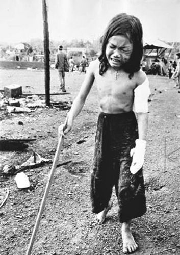 War is a racket, kept going by soldiers. This 12-yr-old girl with a cross around her neck and with multiple wounds uses a stick to hobble through debris in Dong Xoai. Her father, sister and a brother were killed and their home destroyed. Photo by Horst Faas 1965.