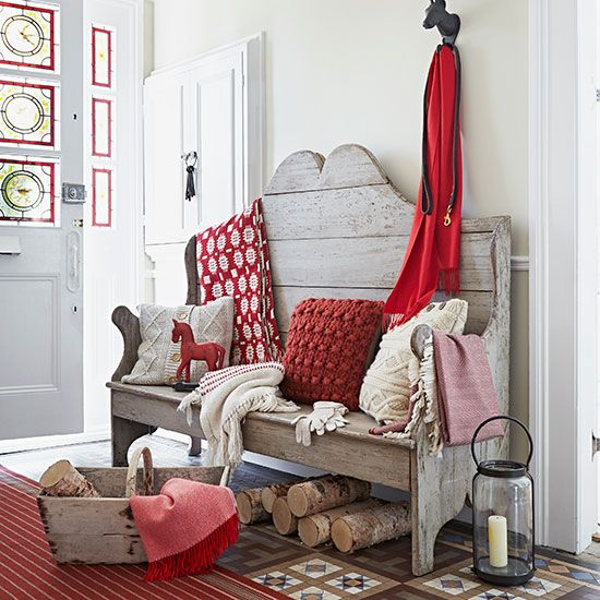 Wooden indoor bench with red and cream cushions