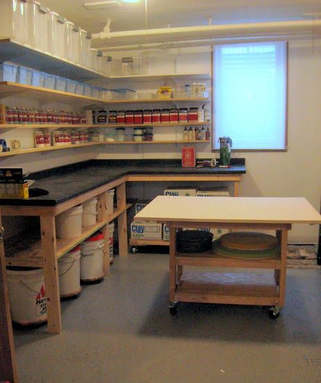 Small studio. Glaze bucket storage under counter, rolling work table. Very efficient organization.