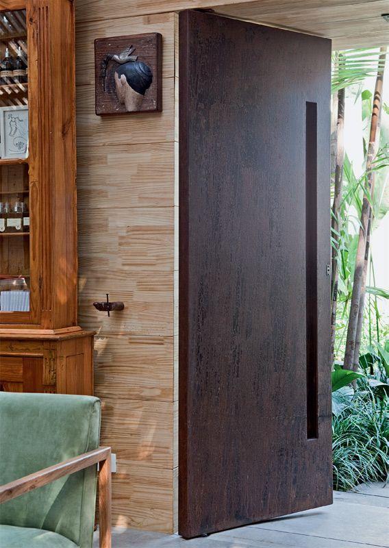 Em contraste com a madeira das paredes, a designer de interiores Marina Linhares encomendou portas de metal à Carvalho Carvalho Serralheria.As duas folhas de 2,35 x 0,85 m são de chapas dobradas de aço-carbono recobertas por aço corten