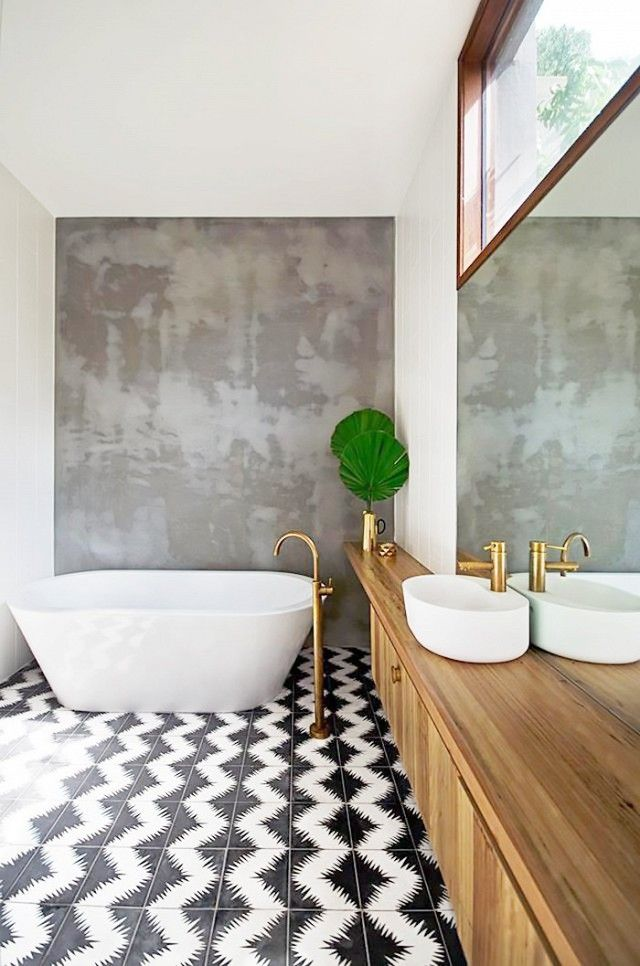 Stand alone white bathtub, black and white tile