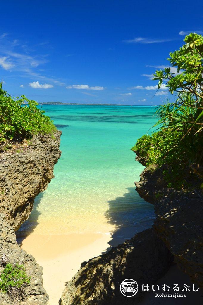 黒島の琉球石灰岩の崖の割れ目から撮影した小浜島。 白い砂浜の先には八重山ブルーの海、そして水平線と重なるように小浜島を望むことができます。