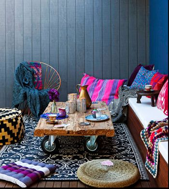 Mixing darks and brights; natural wood, rugs, cushions, a fabulous way to decorate that outdoor space under the pergola