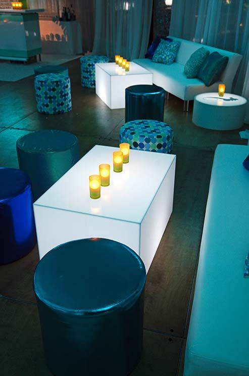 Amp up the mood of a cocktail space with glowing tables, candles and blue-toned lighting.