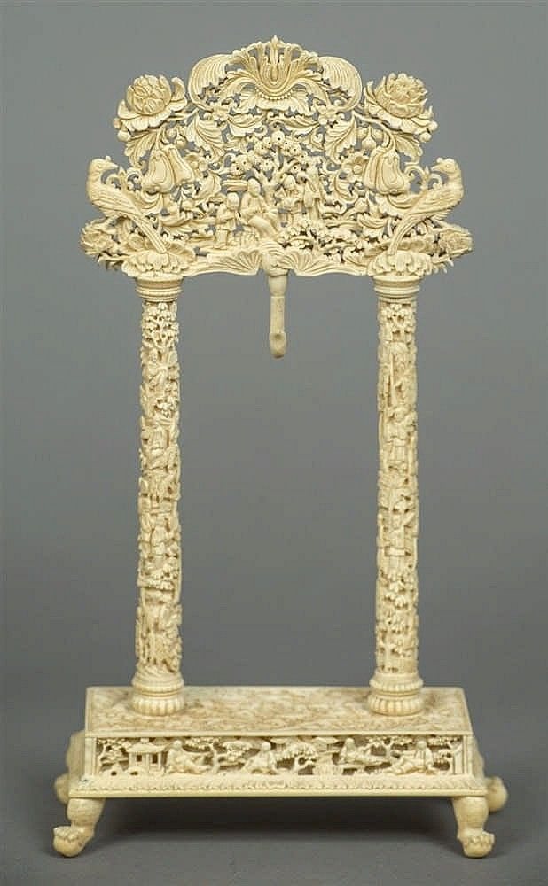 A late 19th century Canton carved ivory watch stand Of portico form, intricately carved with figures and pagodas amongst flowering landscapes, standing on a plinth base with ball and claw feet. 26.5 cm high.