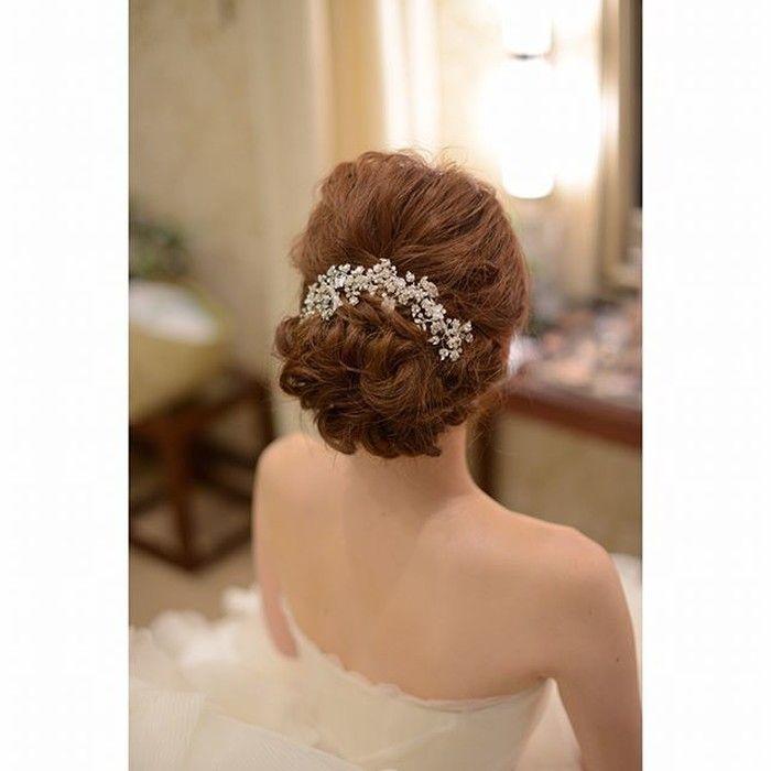 卒花嫁「e.y.wedding」さまは、カジュアルでいながらも清楚な花嫁を目指したヘアスタイルにと、波ウェーブのシニヨンを選ばれたそうです。キラキラと輝くビジューのヘッドアクセサリーが華やぎを添えていますね。