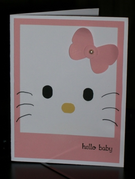 looked up Hello Kitty on Sizzix and noticed that the eyes and nose were the same size and a long oval. The closest thing I could come up with was our Word Window Punch.    The best way to get equal sizes is to put a Post it Note on top of your black cardstock and punch with the sticky on one end. Then push that end through the side, and punch out the shape you need. Save the Post it Note shape. Punch out a word window shape and stick the small Post it piece to it so you can cut out another…