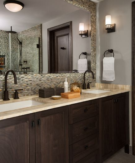 River rocks act as a backsplash and entire wall accent in this master bath. The frameless mirror floats proud of the stones and is backlit with LED lights. The dark espresso cabinets are topped with silver travertine. Dayna Flory Interiors Dayna Rasschaert - Birmingham, MI