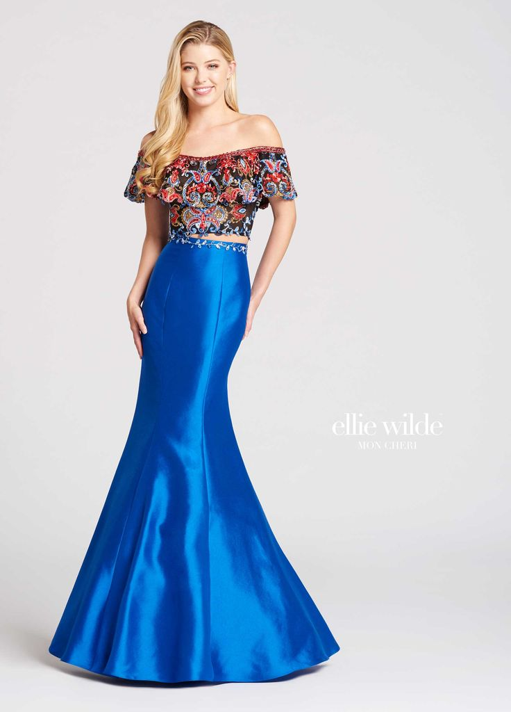 Ellie Wilde EW118025 - Two-piece off-the-shoulder lace and Mikado trumpet gown with straight neckline outlined by beaded lace. Top features embroidered lace scallop edged flounce ruffle over embroidered lace bodice with lace edge ends at natural waistline. High-waisted Mikado skirt features embroidered lace around top edge to create a faux belt and is fitted through the hips and upper thighs before flaring out into a full skirt.