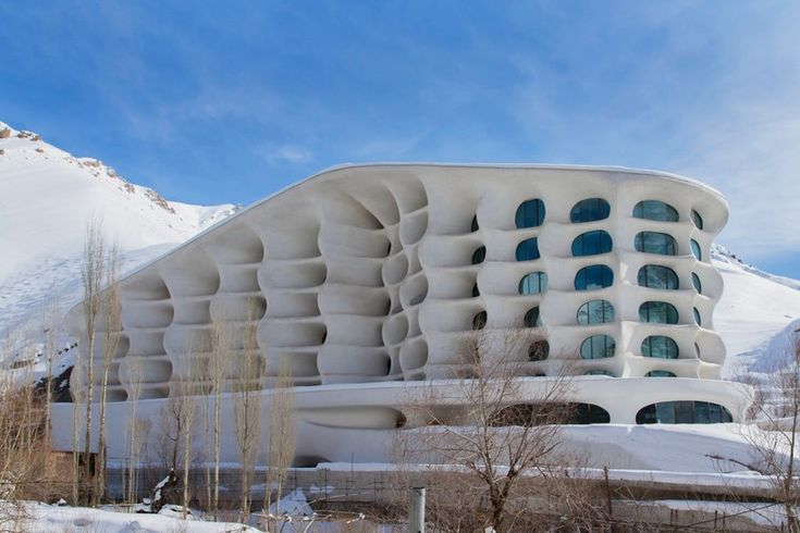 the architecture references an iced-rock formation that appears to be windswept onto the mountainside, providing skiers with a warm, cave-like facility.