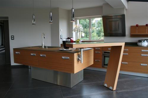 Aménagement cuisine à ambiance contemporaine- Très tendance, tant par son design contemporain que par son implantation ouverte sur le séjour, cette cuisine allie élégamment modernité et convivialité. Le bar pivotant parfait le tout pour en faire une cuisine ergonomique.