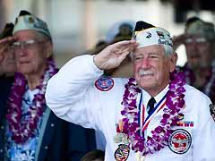 Pearl Harbor survivors stand at attention during a memorial ceremony on December 7, in Pearl Harbor, Hawaii.