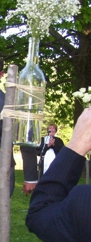 wine bottle vases on sticks for the aisle!