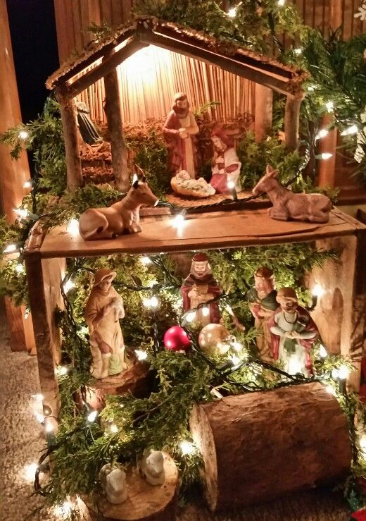 Nativity on top of old peach crate with cedar limbs and white lights...
