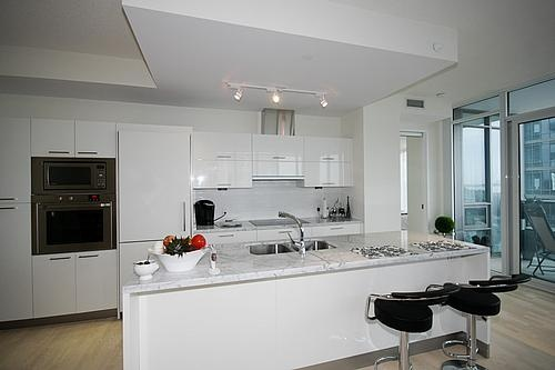 My dream kitchen: sleek white gloss cabinets, marble counters, stainless steel euro-style appliances, & a breakfast bar for my guests to hang out at!
