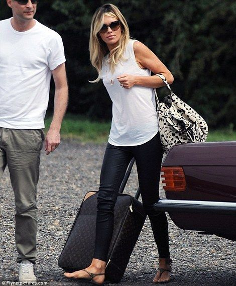Abbey Clancy, with her animal-print Alaïa bag, in sleeveless white shirt, black leather leggings, and sandals.