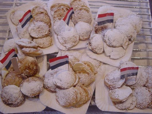 Poffertjes, small Dutch puffed pancakes with melting butter and dusting sugar