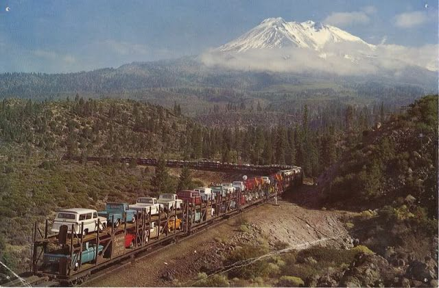 """A Southern Pacific """"Auto-Pack"""" train passing California's Mt. Shasta enroute to Portland carrying new Chevy trucks ca. 1950s-60s"""
